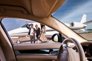 Man and woman departing jet and saying hello while chauffer waits in car.