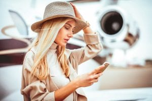 woman with hat looks at Jet Linx Mobile App on phone