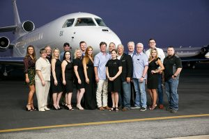 Team members from Jet Linx Austin stand in front of a private jet.