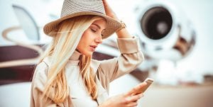 Private jet traveler booking Jet Linx services on her mobile app.