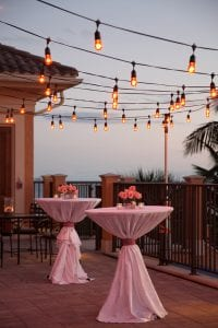 An oceanside veranda with two cocktail tables underneath twinkling lights.