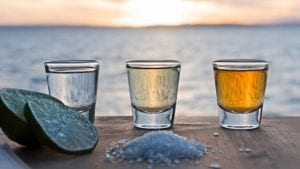 shot glasses of tequila with salt and lime on a wooden table on a beach