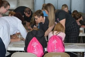 volunteers help girls in aviation day participants with their activities