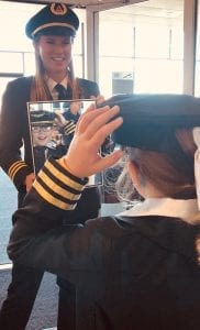 young Girls in Aviation Day participant lights upseeing her reflection in uniform