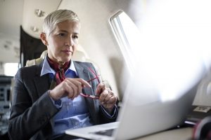 Senior woman sitting inside private jet airplane and working during the flight